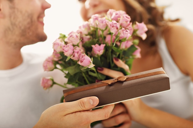 Picture showing man giving flowers and present to woman in bed