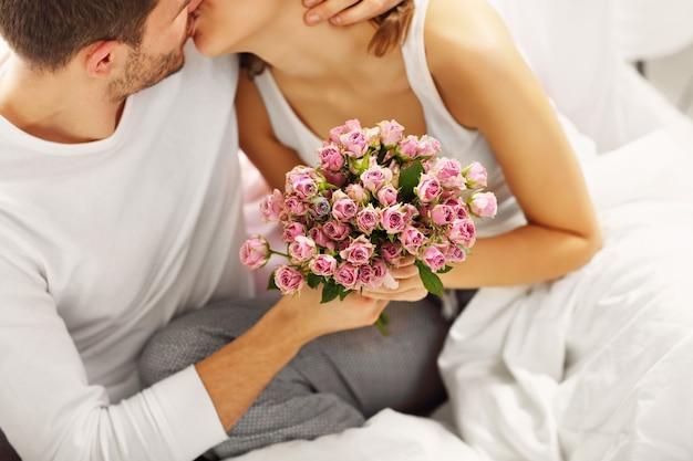 Картинка, на которой мужчина дарит цветы женщине в постели