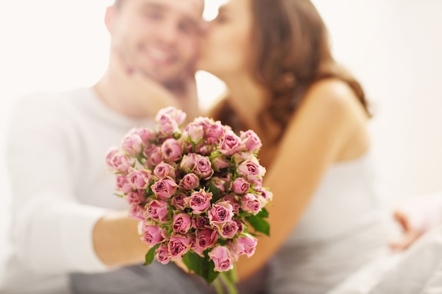 Picture showing man giving flowers to woman in bed