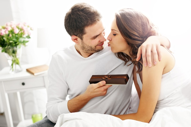 Picture showing man giving present to woman in bed