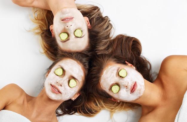 白い背景の上に顔のマスクを持つ3人の友人を示す画像