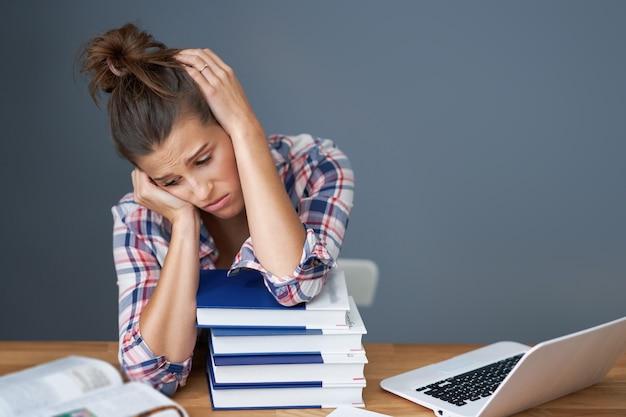 家で遅くまで勉強している疲れた女子生徒の写真
