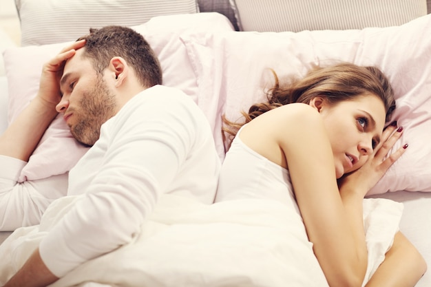 Picture showing unhappy couple argueing in bed