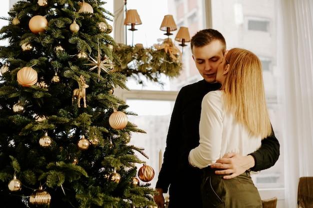Фотография, показывающая молодая влюбленная пара, обнимающаяся над елкой