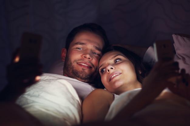 夜のベッドでスマートフォンを使用して若いカップルを示す写真