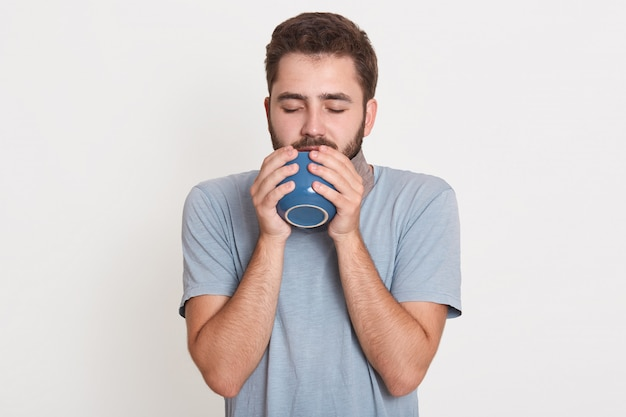 Picture of sleepy dreamy peaceful young man closing eyes, drinking coffee, posing isolated over white wall in