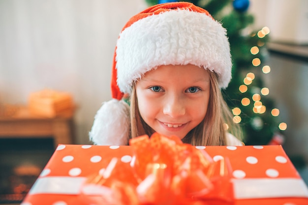 Picture of small and beautiful girl holding read box with present