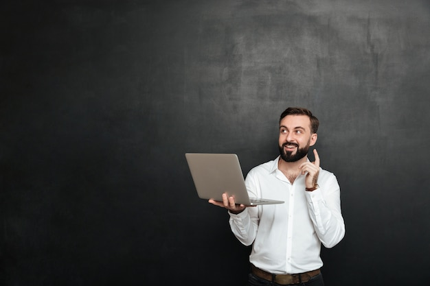 Picture of smart brunette man have idea gesturing with finger up while using silver laptop, isolated over dark gray wall