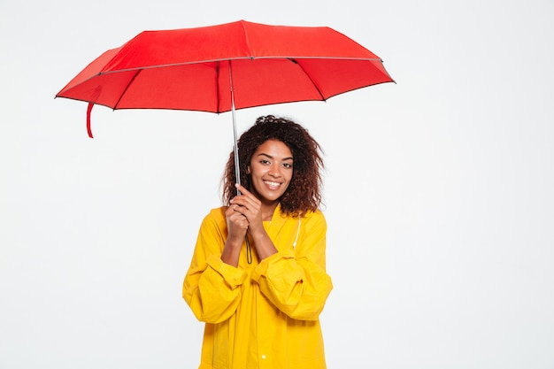 Picture of smiling african woman in raincoat hiding under umbrella over white