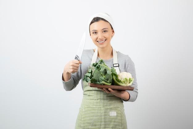 Immagine di una donna attraente sorridente che tiene un coltello con un piatto di legno di cavolfiori