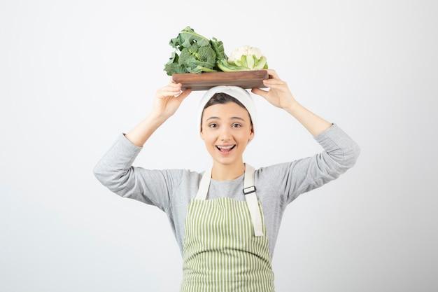Immagine di una donna attraente sorridente che tiene un piatto di legno di cavolfiori sopra la testa