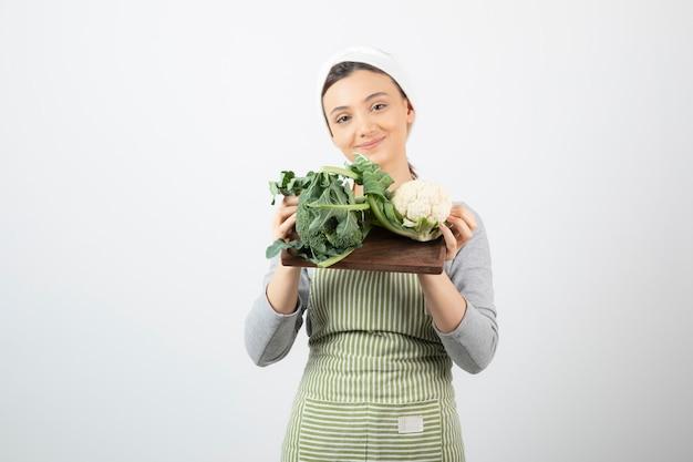 Immagine di una donna attraente sorridente che tiene un piatto di legno di cavolfiori