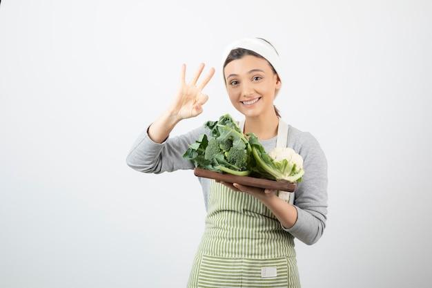 Immagine di una donna attraente sorridente con un piatto di legno di cavolfiori che mostra il numero tre