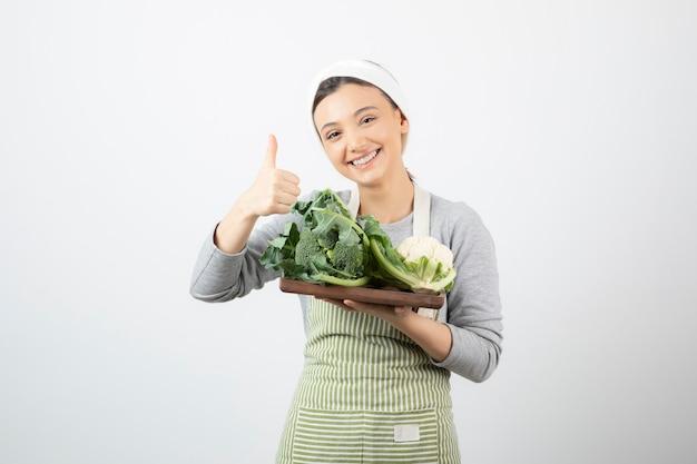 Immagine di una donna attraente sorridente con un piatto di legno di cavolfiori che mostra un pollice in su
