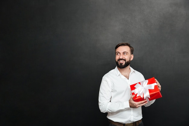 Picture of smiling bearded man holding red gift box with white ribbon and looking aside over dark gray wall