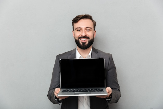 Picture of smiling bearded man holding silver personal computer showing black screen and looking on camera, isolated over gray wall