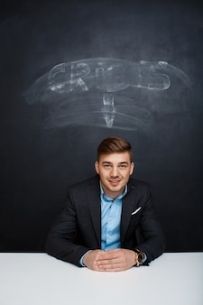 Picture of smiling man over blackboard with crisis inscription