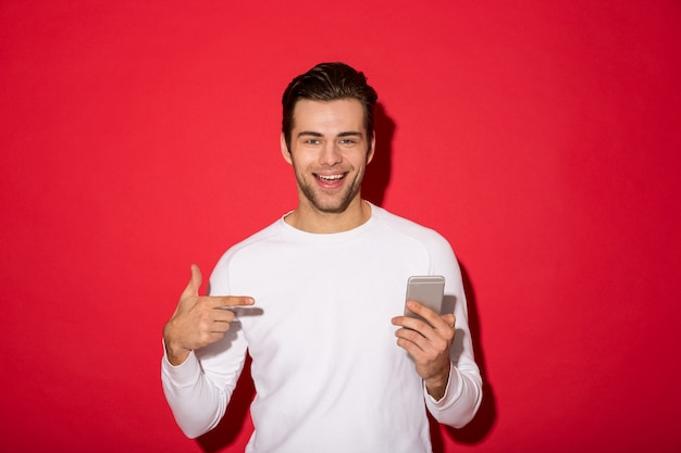 Picture of smiling man in sweater looking while holding smartphone and pointing at him over red wall