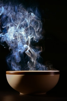 Picture of smoke rising from the food above the cup the concept of hot food.