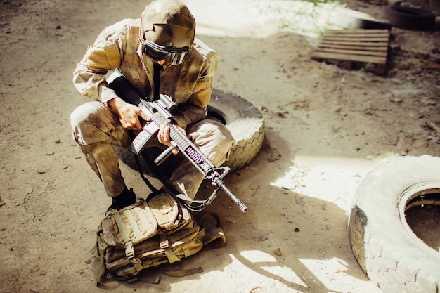 A picture of soldier sitting on the ground and wearing face mask. he is holding black rifle in hands. man is looking odwn to bag. he has some rest.