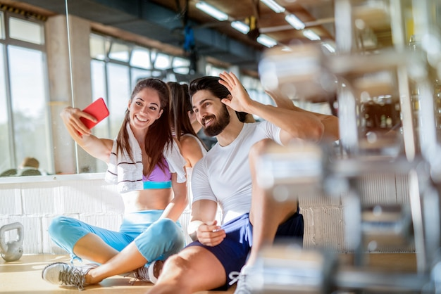 Picture of sporty beautiful fit couple sitting in bright gym and taking photo of them self. smiling and looking at telephone.