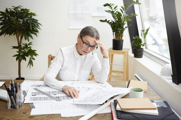 Picture of stressed upset middle aged female engineer wearing white shirt and spectacles looking at blueprints or project documentation in front of her on desk, frustrated to see so many mistakes