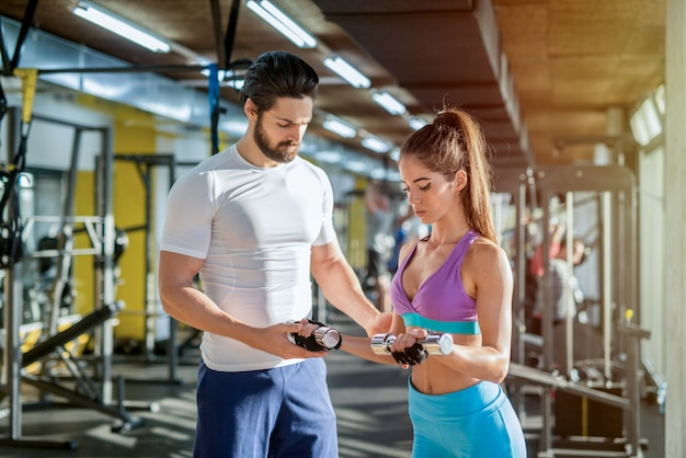 Picture of strong personal trainer helping his female client weights in gym.