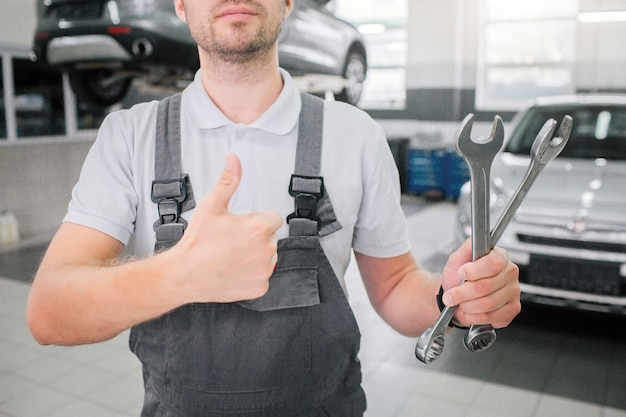 Picture of strong young man stands and shows big thumbs up. also he holds two wrenches in left hand. there are tow cars behind him. one of them is on platform.
