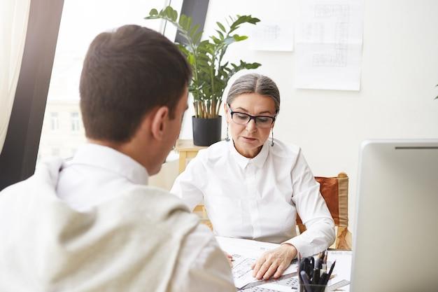 Foto di elegante capo architetto femminile di 50 anni in occhiali che rivede i disegni di un impiegato maschio brunetta irriconoscibile, studiando la documentazione sulla scrivania, avendo un'espressione facciale concentrata seria