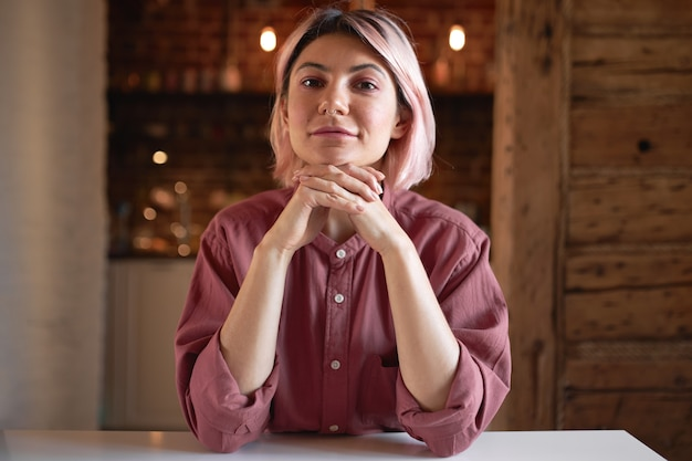 Picture or stylish confident young 20 year old woman copywriter wearing cotton shirt and nose ring holding clasped hands under chin, smiling, working from home, sitting comfortably at white table