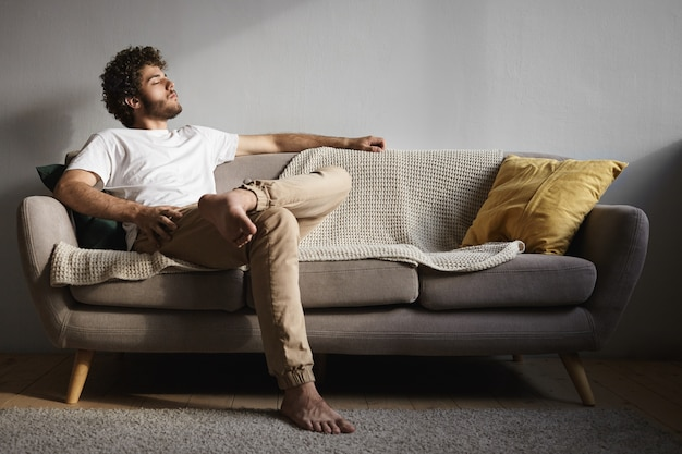 Picture of stylish handsome young guy with fuzzy beard, voluminous hairdo and bare feet keeping eyes closed, falling asleep or listening to classical music, enjoying leisure time, sitting on couch