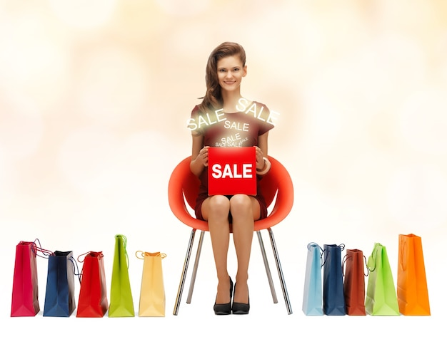 Picture of teenage girl in red dress with shoes, bag and sale sign