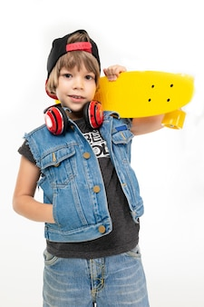 Picture of a teenager boy in denim jacket and shorts, black cap, with yellow penny and earphones keeps his hand in pocket