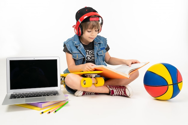 Picture of a teenager boy sits on floor in denim jacket and shorts. sneakers with yellow penny, red earphones, laptop and do homework isolated