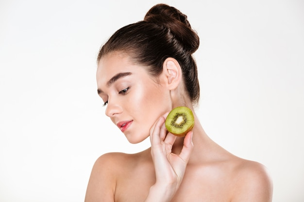 Picture of tender woman having clean skin posing with closed eyes holding ripe juicy kiwi in hand