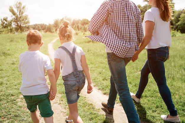 A picture that was made from the back. happy family is walking together through meadow. boy is holding hand of his sister while man is holding hand of his wife. their walk is confident.