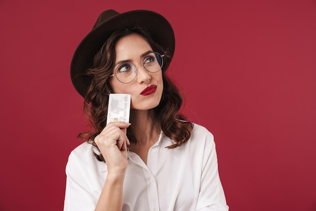 Picture of thinking thoughtful young woman in glasses isolated on red wall holding credit card.