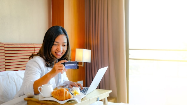 Picture of tourists used laptop and eating breakfast on the bed in the luxury hotel room.