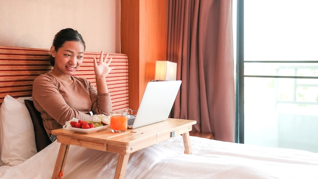 Picture of tourists used laptop and eating fruits on the bed in the luxury hotel room, healthy food concept.