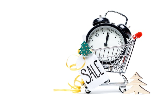 Picture of trolley with gold alarm clock, christmas tree, greeting card, ribbon on blank white. place for text