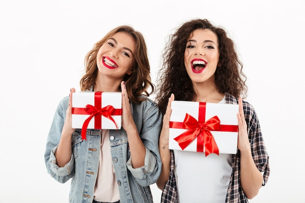 Picture of two happy girls holding gifts in hands  over white wall