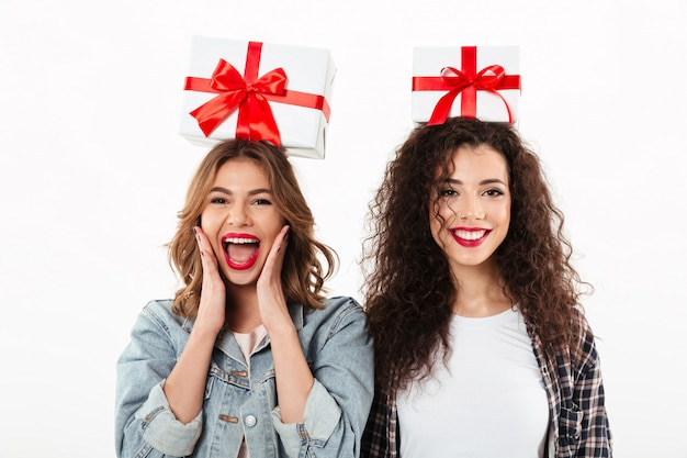 Picture of two joyful girls holding gifts on their heads  over white wall