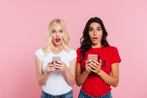 Picture of two pretty shocked women holding smartphones and looking at the camera over pink