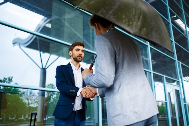 Picture of  two young businessmen meeting at station