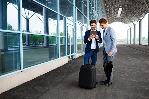 Picture of  two young businessmen talking on rainy station  and holding tablet