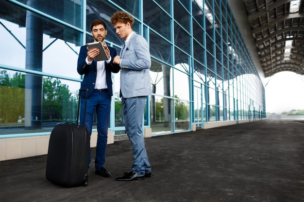 Picture of  two young businessmen talking on station  and holding tablet