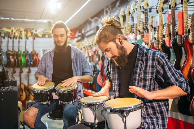 Picture of two young men sitting and having beat on drums. they are in room full of electric guitars. guys play together.