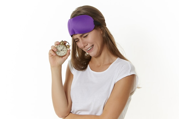 Picture of unhappy young caucasian woman having painful facial expression and crying, holding retro alarm clock, does not want to get up to work so early, feeling sleepy and tired, wearing eyemask