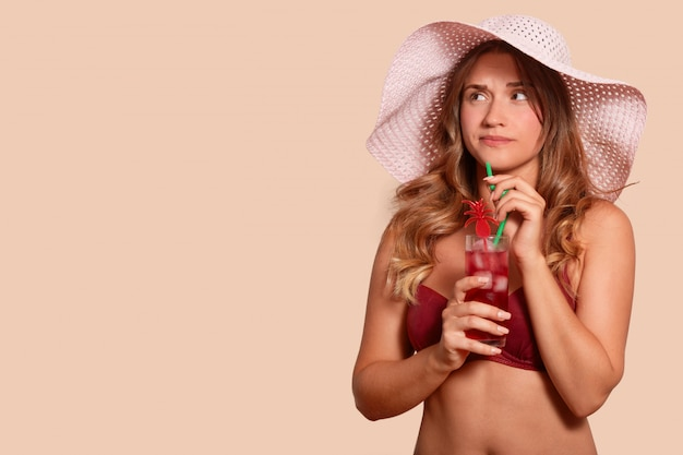 Picture of upset attractive female having unpleasant facial expression, looking aside, being on holidays, holding cocktail, spending time alone, having long fair hair. copy space for advertisement.