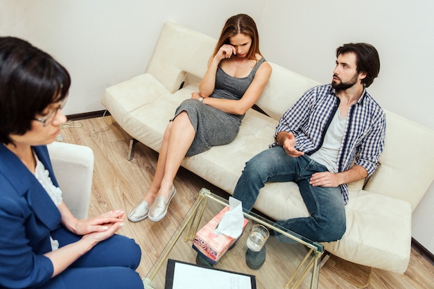A picture of upset woman sitting on sofa and crying. she is wiping her eyes. bearded guy is looking at her. he is upset as well. doctor is sitting in front of them and looking down.